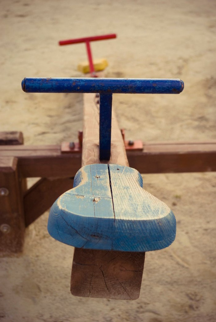 Wooden playground seesaw painted in blue and red.