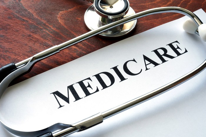 """A stethoscope lies on a table, surrounding the word """"medicare"""" on a sheet of paper."""