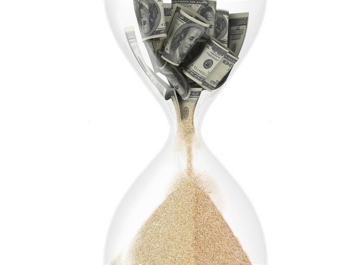 Hourglass with dollars in the top falling below and turning into sand