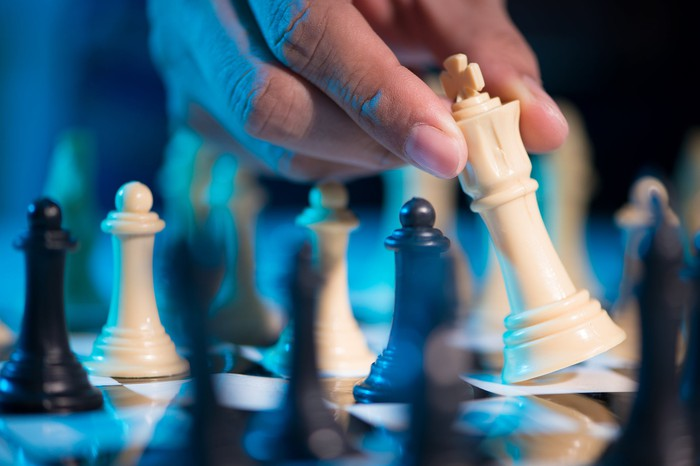 A hand moving the king in a chess game.