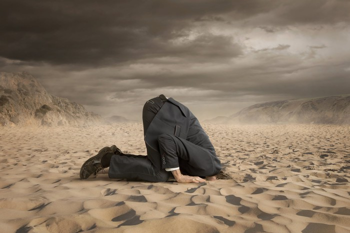 A businessman with his head in the sand, a not-so-good response to a crisis.