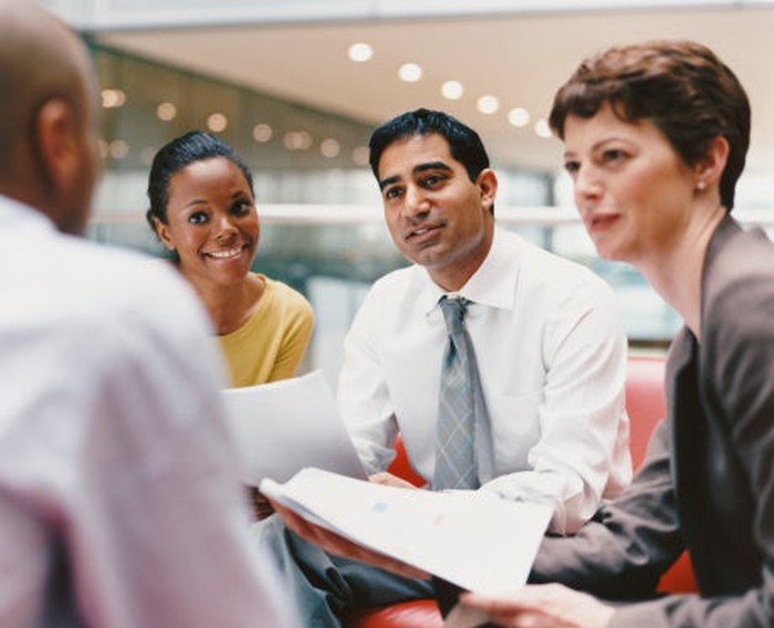 Small group of men and women in an office discussion