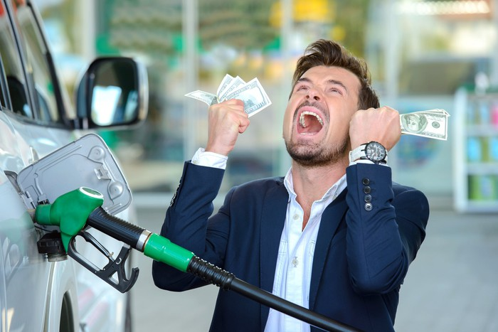 Emotional businessman counting money with gasoline refueling car at fuel station.