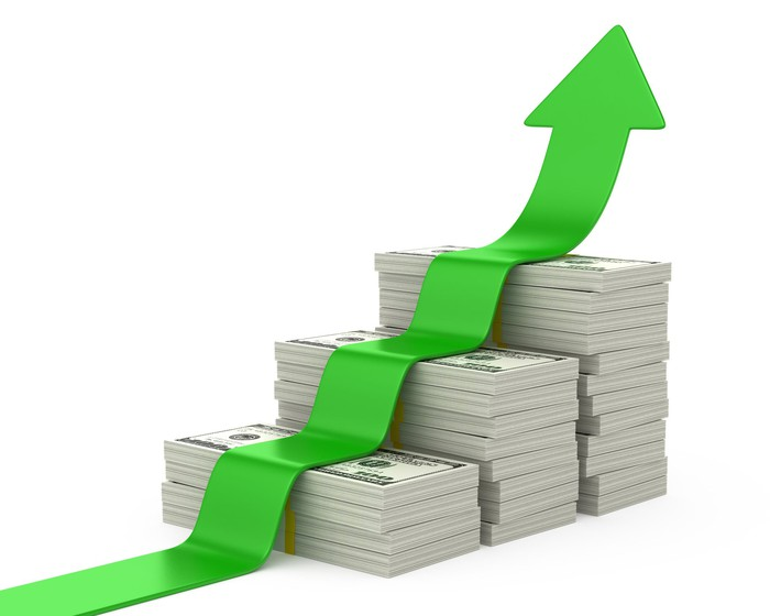 Green arrow rising, on top of growing stacks of cash