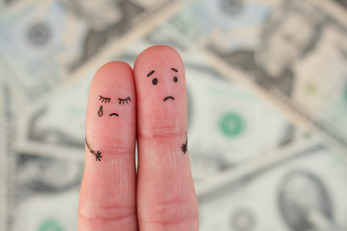 two fingers with sad faces drawn on them, in front of blurry dollar bills