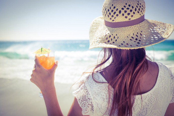 Woman wearing a straw hat drinking a cocktail on a beach