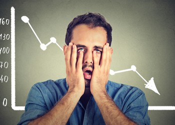 frustrated man in front of stock chart going down crash losses