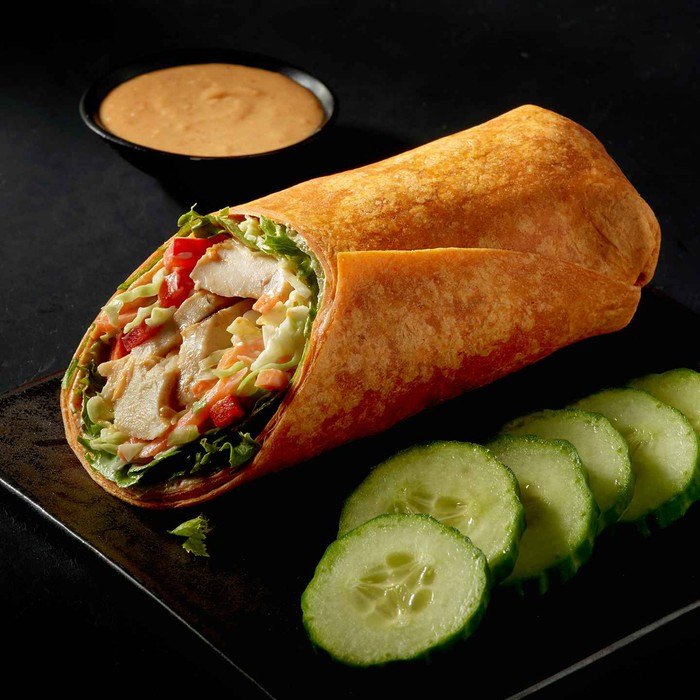 Thai chicken wrap with cucumber slices on the side.