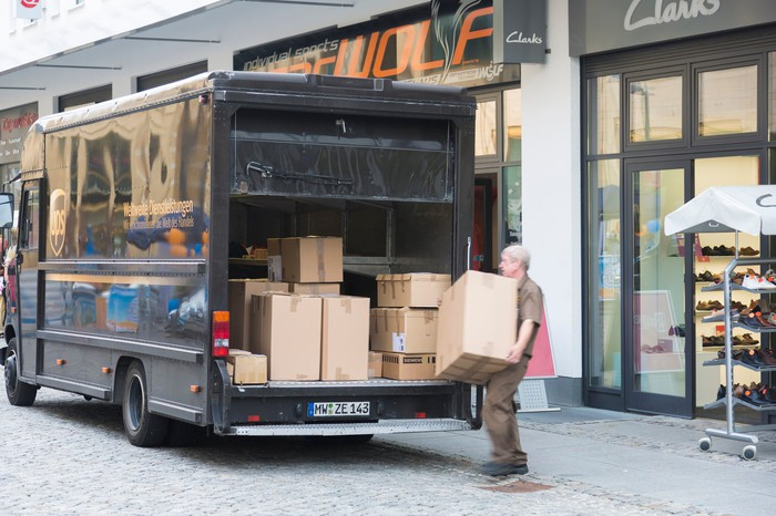 Man picking up a box from the back of a UPS truck
