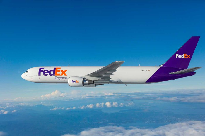 A FedEx Boeing 767 aircraft flying above the clouds.
