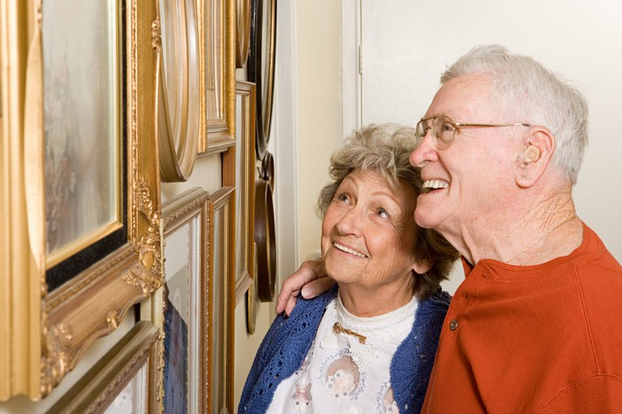 Retired couple looking at framed artwork