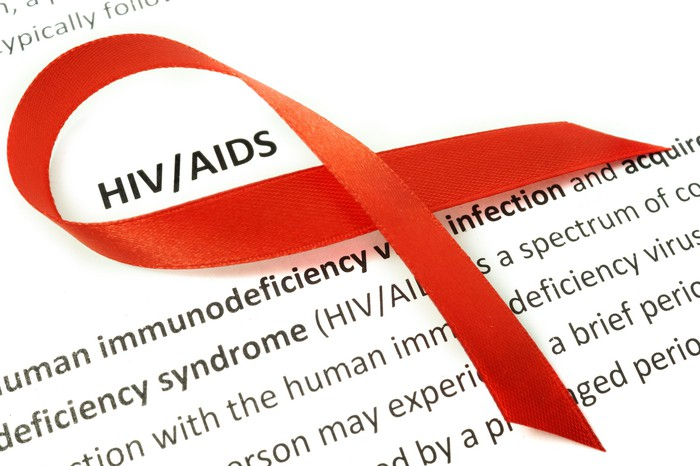 Red ribbon on a paper with definition of HIV/AIDS