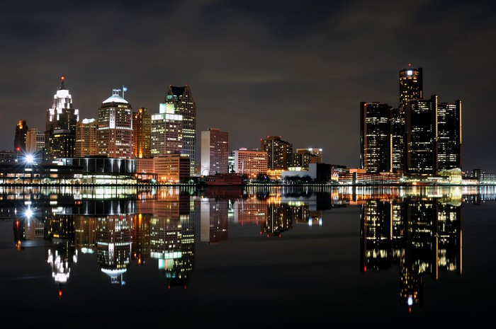 The Detroit skyline at night with it's reflection in the foreground.