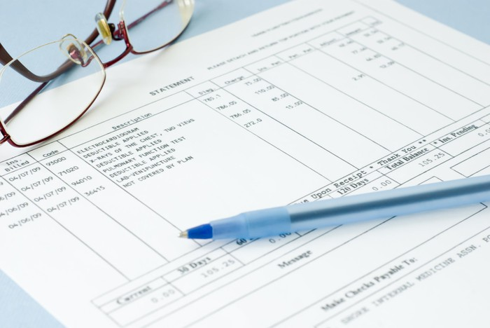 A medical bill, with a pen and pair of glasses lying on top of it.