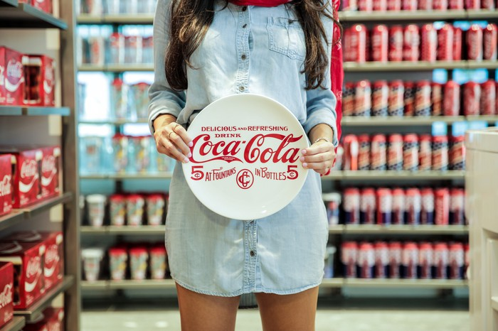 A woman holds a Coca-Cola plate.