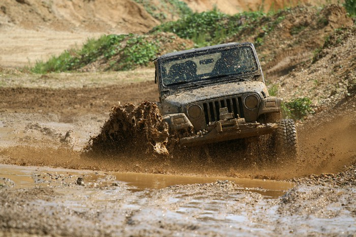 A jeep is driving through mud.