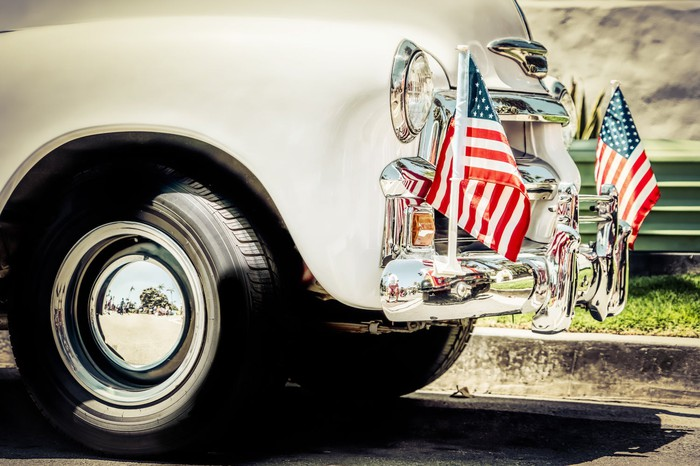 Old car with American flags on the front.