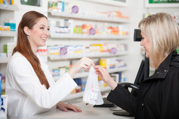 A pharmacist hands medicine to a customer.