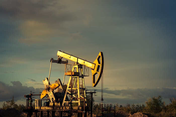 An oil pump jack against a background of sky at sunset.
