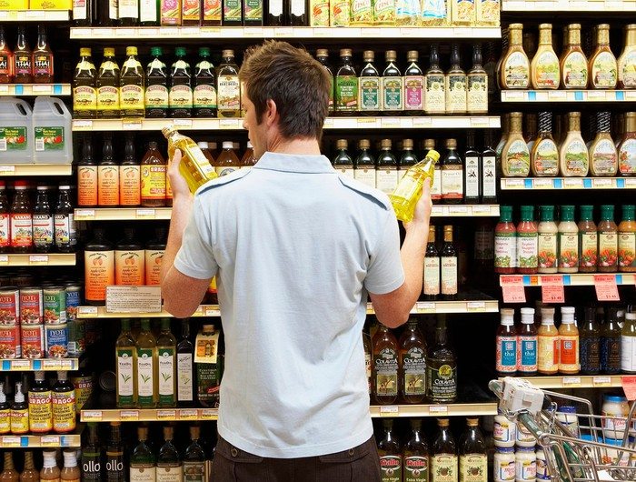A young shopper compares two products in grocery aisle.