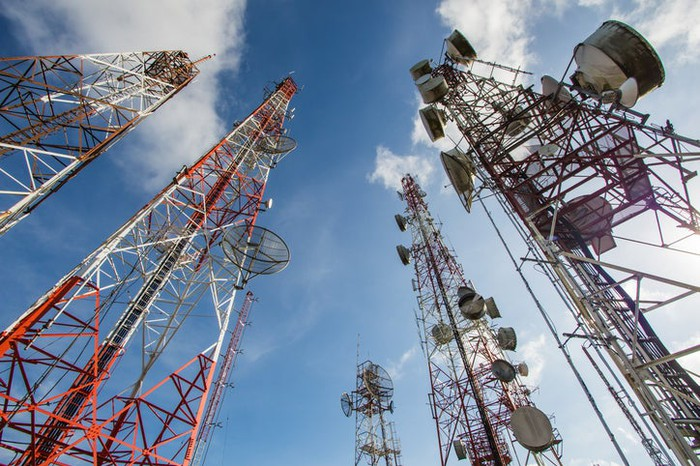 An upward-pointing view of a cluster of telecom towers.