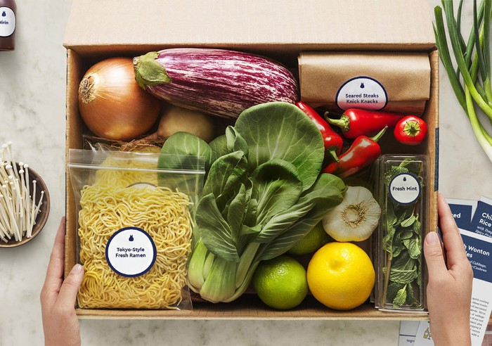 A Blue Apron box containing ingredients for a meal.