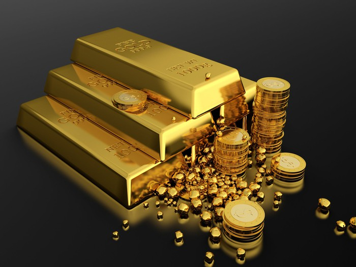 Gold bars are stacked next to gold coins and nuggets.