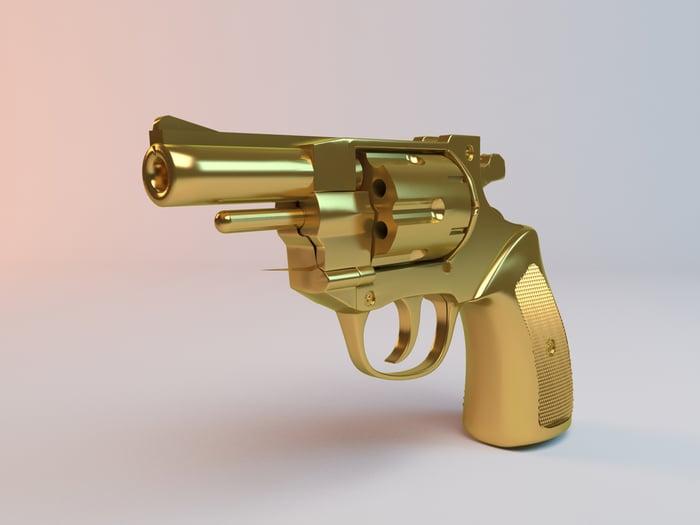 A close-up of a golden pistol.