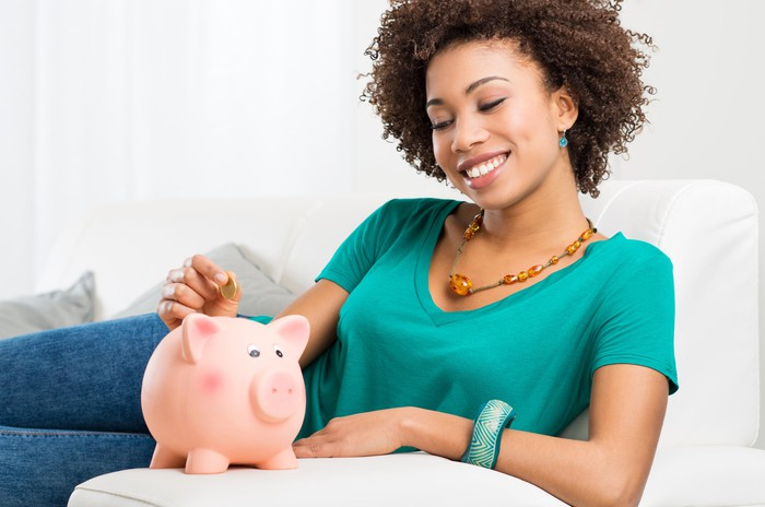 A young woman putting money into a piggy bank.