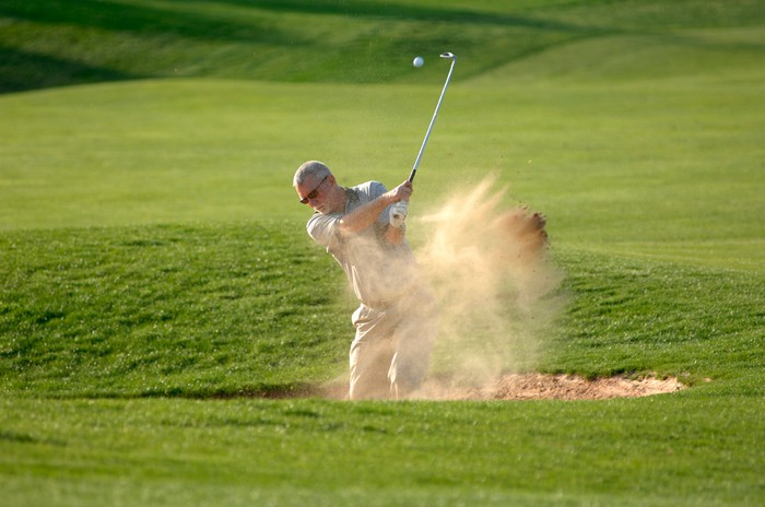 Man golfing in sand trap