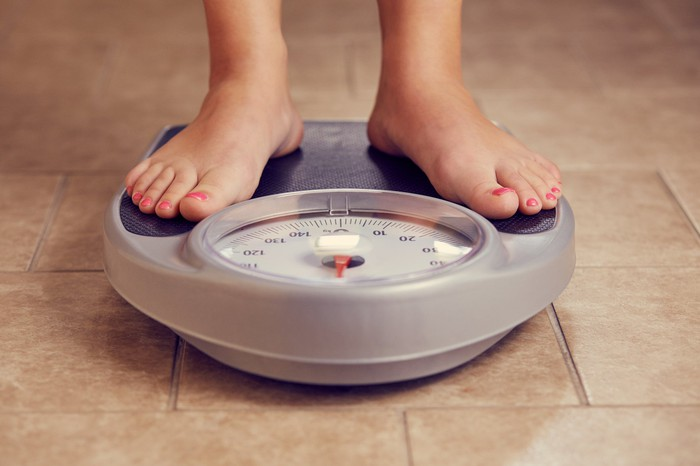 A person stands on a bathroom scale.