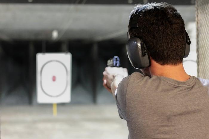 A man at a shooting range aiming at a target.