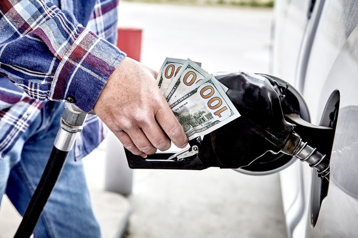 Man holding cash while pumping gas.
