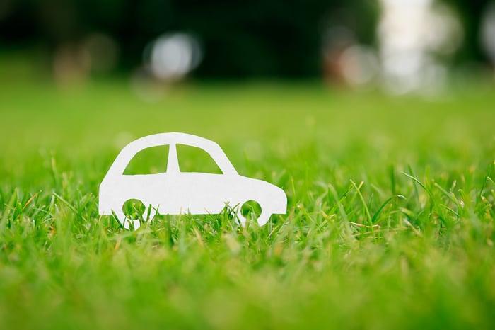 A paper car on a grass lawn.