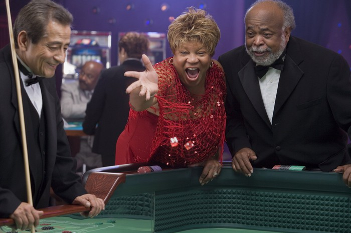 A smiling man and woman play craps at a casino, while the stickman looks on.