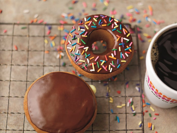 An overhead view of a cup of coffee and two doughnuts, both frosted with chocolate and one covered in colorful sprinkles.