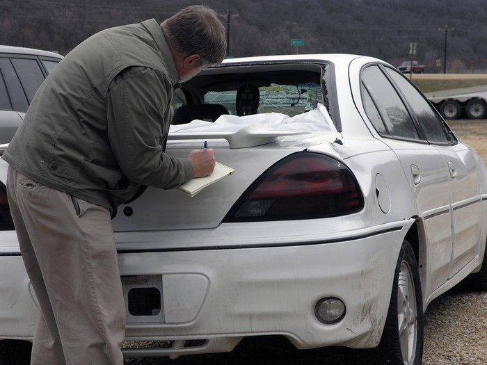 A claims adjuster looks at a car