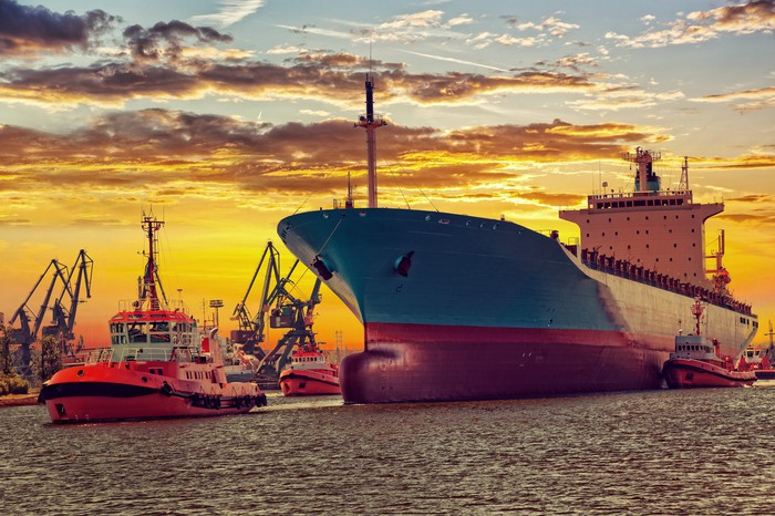 Big ship with escorting tugs leaving port at sunset.