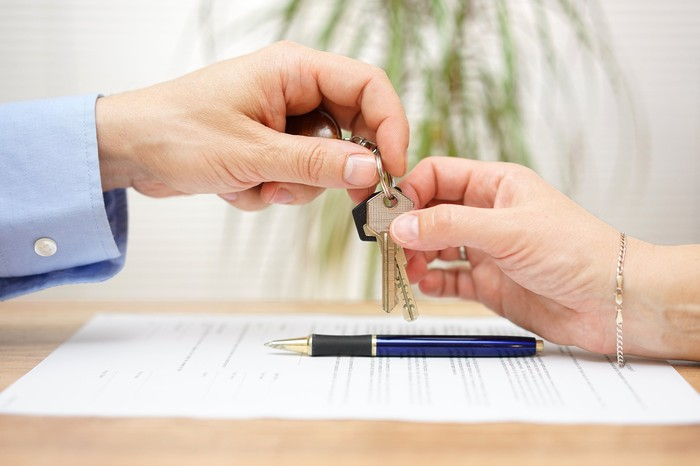 Mortgage closing, with keys being handed over