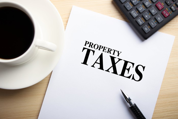 Property tax report with cup of coffee and calculator