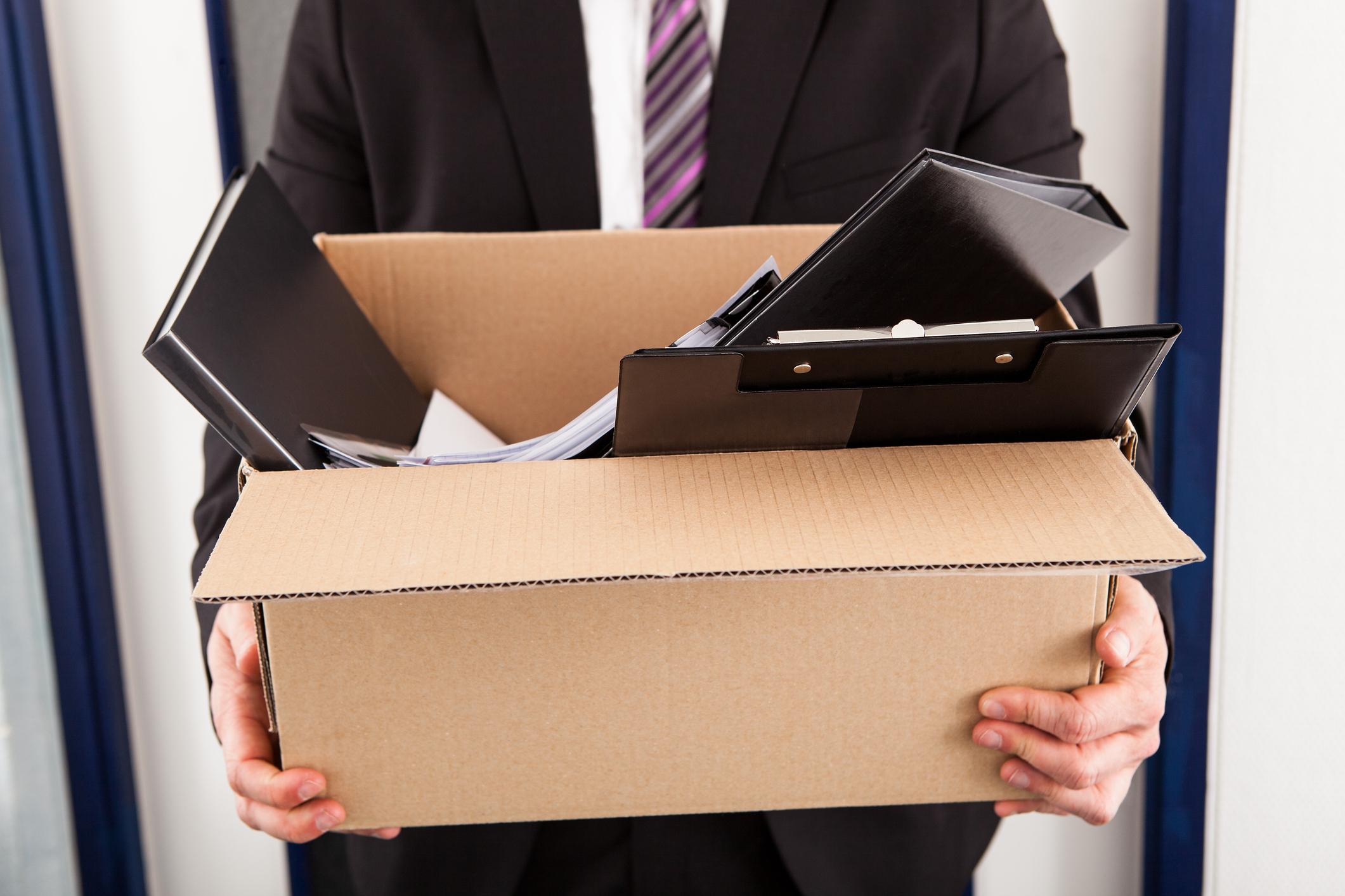 Man in suit walking with cardboard box full of belongings.