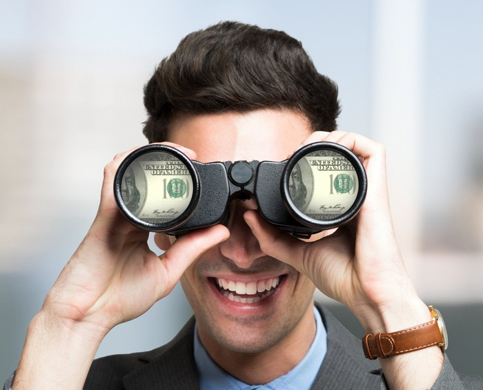 man looking at money through binoculars