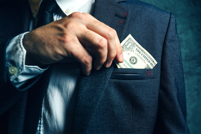 A man puts a dollar bill in his suit pocket.