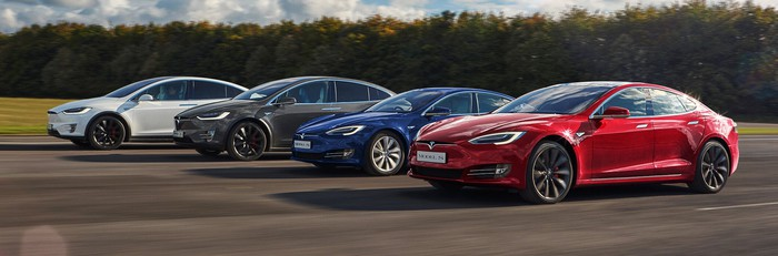 Tesla vehicles driving side-by-side on a road