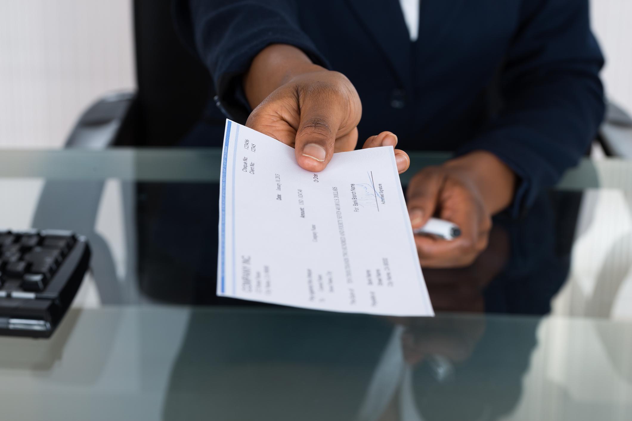 Handing over a payroll check.
