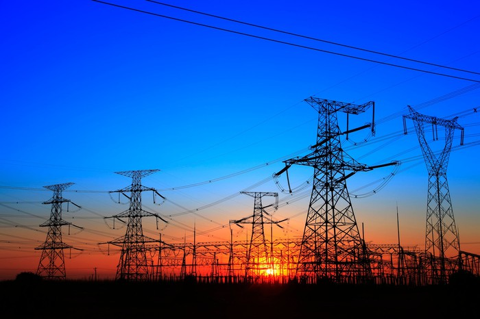 A cluster of transmission towers and power lines at sunset.
