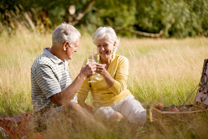 Senior couple toasting outdoors