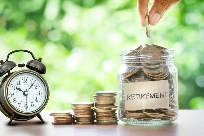 """A hand drops a coin into a glass jar labeled """"retirement,"""" sitting next to stacks of coins and an alarm clock."""