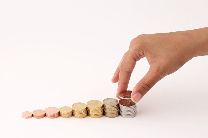 A hand places a coin on the tallest stack of a row of progressively higher groupings of coins.