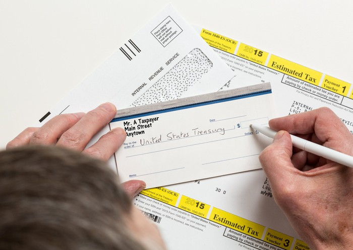 A person filling out a check for their quarterly estimated tax payment to the IRS.